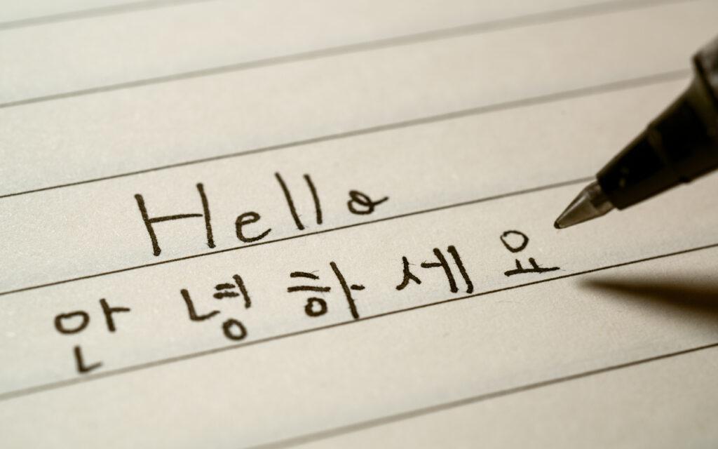 Korean language learner writing Hello word Annyeonghaseyo in Korean on a notebook