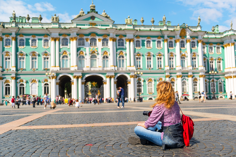 Young woman relax in front of the Winter Palace in Saint Petersburg, Russia