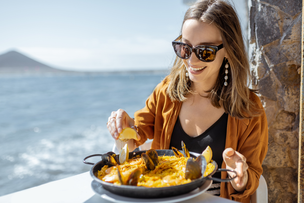 Woman eating paella, while sitting at the restaurant terrace near the ocean.