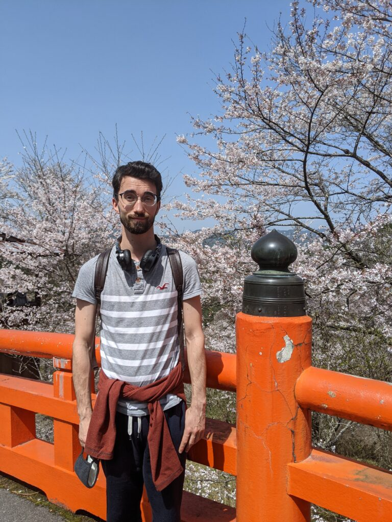 Daniel Mulcahy standing by blossom trees in Kyoto